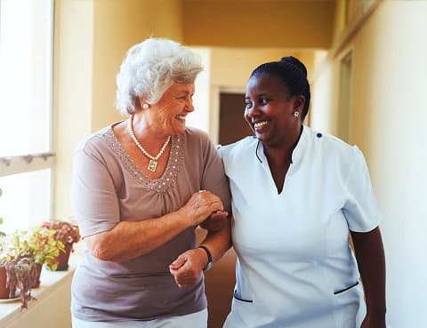 a nurse assisting an old lady walk while and smiling