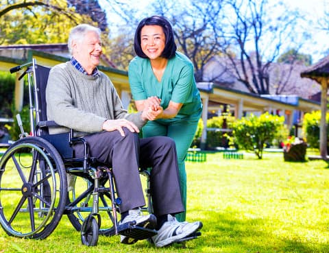 a nurse holding an old man's hand while he's sitting on a wheelchair and smiling